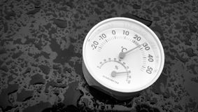 Hygrometer. Analog hygrometer putting on a black background filled with drop of water after rain Royalty Free Stock Photo