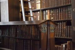 Hylla av gamla böcker i arkiv Arkivbild