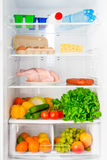 Hylla av kylskåpet med mat Arkivfoto