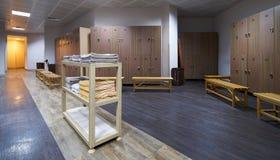 Hylla för rena handdukar i en omklädningsrum med låsbara skåp med träbänkar i luxur Royaltyfria Bilder