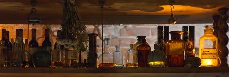 Hylla med alkemi-/apotekflaskor royaltyfria bilder