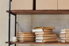 Hylla med askar och böcker arkivfoto