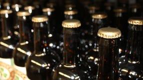 Hylla med flaskor av öl arkivfoto