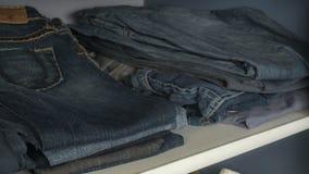 Hylla med jeans i garderoben royaltyfri bild