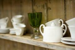 Hylla med koppar och exponeringsglas Royaltyfri Foto
