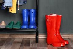 Hylla med olika skor och röda gummistöveler arkivbild