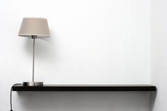 Hylla på väggen med lampan Royaltyfri Bild