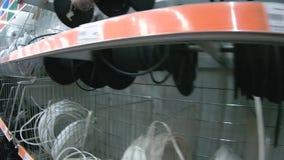 Hyllor med elektriska trådar i supermarket lager videofilmer