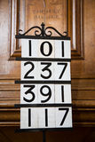 Hymn Numbers in Church. Hymn board with four Hymn numbers set against a traditional wooden pulpit with the Holy Bible inscribed into it, London, England, UK Royalty Free Stock Photos