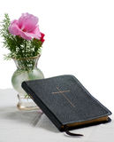 Hymnal with flowers. Old black leather Christian hymnal with cross on the front, leaning against vase with pink and red flowers and greenery, with a white Stock Photo