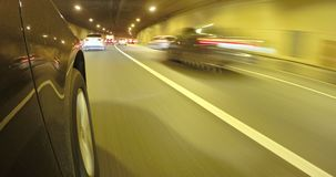 The drive in the tunnel. Hyper laps footage of the drive car in the tunnel with the exit out into the bright light it the end. The rotation of the wheel in the stock footage