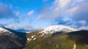 Hyper lapse of clouds running on blue sky over amazing landscape of high snowy mountains and coniferous forest on the stock video