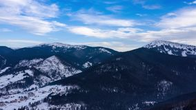 Hyper lapse of clouds running on blue sky over amazing landscape of snowy mountains and coniferous forest on the slopes stock footage