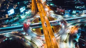 Hyper lapse time-lapse of car traffic transportation above circle roundabout road in Asian city. Drone aerial view fly in circle