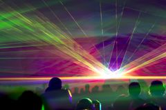 Hyper laser show. Very colorful show with a crowd silhouette and great laser rays at youth party festival Royalty Free Stock Image