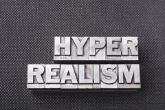 Hyper realism bm. Hyper realism phrase made from metallic letterpress blocks on black perforated surface Stock Image
