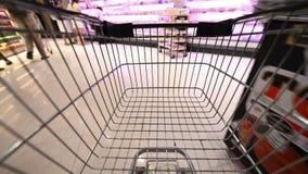 Hyper schackningsperiod för tid 4K av shoppingvagnen till och med gångarna av en supermarket lager videofilmer