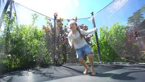 Hyperactive girl acrobatic jumping on outdoor trampoline. Handheld shot. Hyperactive girl acrobatic jumping on outdoor trampoline. Happy child have fun on sunny stock video