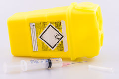 Hyperdermic needle and sharps bucket royalty free stock photography
