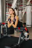 Beautiful sportive woman in gym. Hyperextension, sports young woman doing exercises strengthens the abdominal muscles and back muscles royalty free stock image