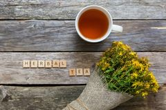 Hypericum - St Johns wort plants wrapped in canvas on wooden board table with cup of herbal tea, top view. royalty free stock photos