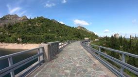 Hyperlapse che cammina sulla parete di una diga di un lago artificiale alpino Alpi italiane Orobie L'Italia Punto di vista della  archivi video