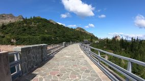 Hyperlapse walking on the wall of a dam of the an Alpine artificial lake. Italian Alps. Orobie. Italy. Hiker POV point of view. Summer time stock footage