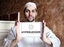 Hyperledger logo. Logo of Hyperledger on samsung tablet holded by arab muslim man. Hyperledger is an umbrella project of open source blockchains and related Stock Image