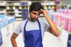 Hypermarket arbeider wat betreft voorhoofd als spanningsconcept stock fotografie