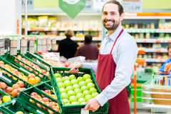 Hypermarket clerk filling up storage racks Royalty Free Stock Images