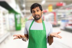 Hypermarket employee with confused expression. Indian male hypermarket or supermarket employee wearing green apron with confused expression making not-knowing royalty free stock images