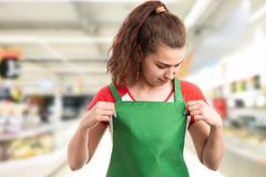 Hypermarket employee fixing apron royalty free stock photography