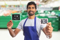 Hypermarket employee holding boards with for sale and per cent. Smiling friendly indian male hypermarket or supermarket employee holding boards with for sale royalty free stock image