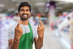 Hypermarket employee holding fingers crossed. Hypermarket or supermarket male indian employee holding fingers crossed at both hands with trustworthy expression stock photo