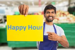 Hypermarket employee holding happy hour paper. Smiling hypermarket or supermarket indian male employee holding and pointing at happy hour yellow paper with index royalty free stock photo