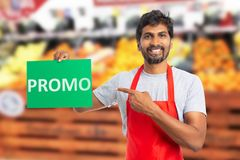 Hypermarket employee presenting paper with promo text. Trustworthy indian male hypermarket or supermarket employee presenting red paper with promo text on it stock image