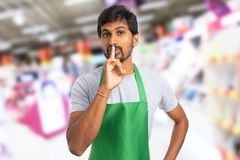 Hypermarket employee showing keep quiet gesture. Indian hypermarket or supermarket male employee showing keep quiet gesture with index finger on lips stock image