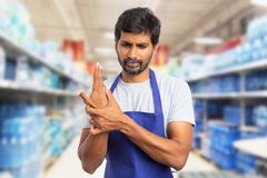 Hypermarket employee touching sprained wrist royalty free stock photos