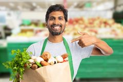 Hypermarket employee pointing at bag with vegetables. Hypermarket or supermarket indian male employee using index finger for pointing at paper bag with stock photos