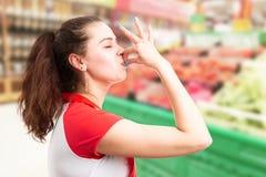Hypermarket werknemer die heerlijk gebaar maken stock fotografie
