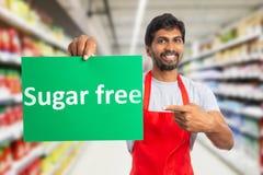 Hypermarket werknemer die suiker vrije teksten op papier tonen royalty-vrije stock afbeeldingen