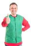 Hypermarket werknemer die thumbup of tonen als stock afbeeldingen