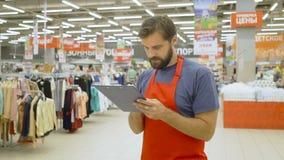 Hypermarket werknemer in rode aoprt met klembord in supermarkt stock videobeelden