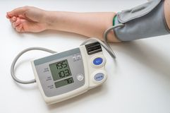 Hypertension concept. Man is measuring blood pressure with monitor. On white background royalty free stock photography