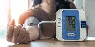 Hypertension or high blood pressure illness in patient with blood pressure monitoring, measurement on digital sphygmomanometer