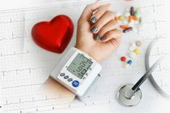 Hypertensive heart disease concept with woman's arm measuring blood pressure royalty free stock images