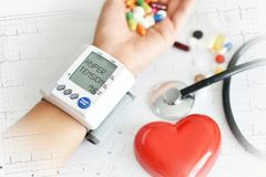 Hypertensive heart disease concept with woman's arm measuring blood pressure stock photos
