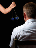 Hypnosis. Woman hypnotizes man with a swinging watch during hypnotic treatment stock photos