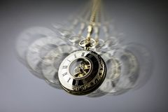 Hypnosis pocket watch. Hypnotism concept, gold pocket watch swinging used in hypnosis treatment Royalty Free Stock Image