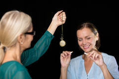 Hypnotherapist holding pendulum by patient Stock Photos